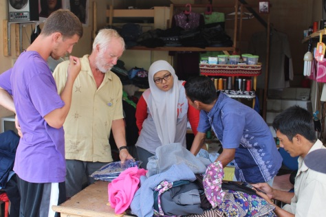 With Tiwi's help, Tim and Jesse explain to the tailor that they want basketball jerseys made of the batik material they bought.
